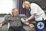 Mitarbeiterin des ambulanten Pflegedienstes beim Blutdruckmessen